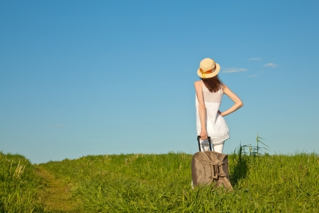 Beautiful young lady travelling with a suitcase, rear view photo