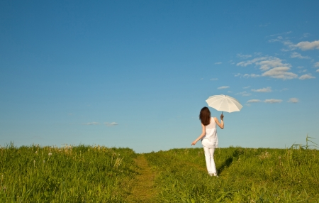 Beautiful girl with white umbrella walking through the summer meadow photo