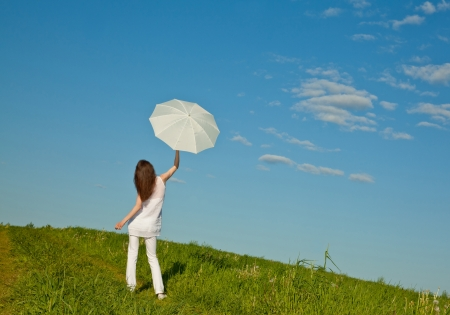 Beautiful brunette girl with white umbrella in a green summer meadow photo