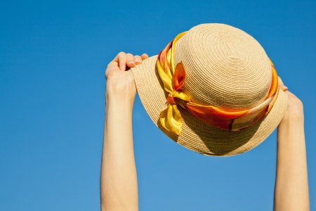 Womans summer hat in hands of a traveller against blue sky Stock Photo