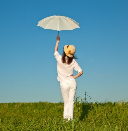 Beautiful girl with white umbrella in summer meadow Stock Photo - 14001342