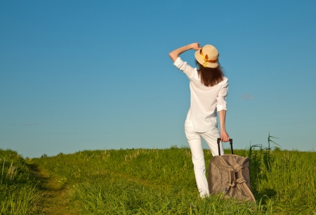 boundless: Beautiful young woman with a suitcase looking at horizon - rear view