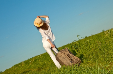 Beautiful young woman with a suitcase looking at horizon - rear view photo