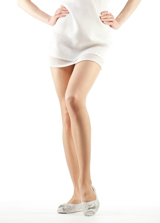 Beautiful womans legs; legs of a girl wearing mini and flat shoes - closeup shot on white background Stock Photo