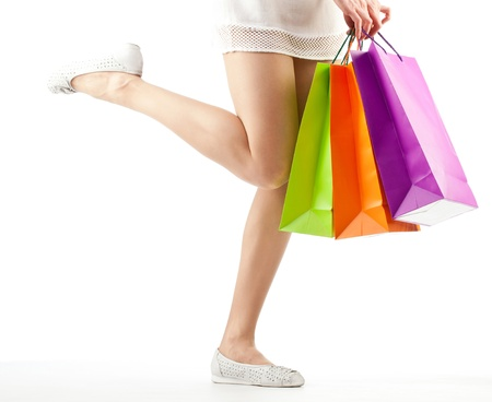 Girl holding multicolored shopping paper bags - closeup shot on white background Stock Photo - 14033043