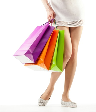 Girl holding multicolored shopping paper bags - closeup shot on white background photo