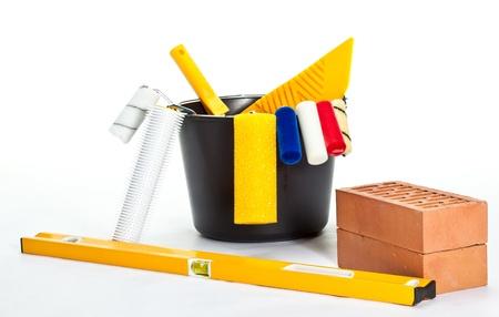 Construction (painting) tools, level and bricks on white background photo