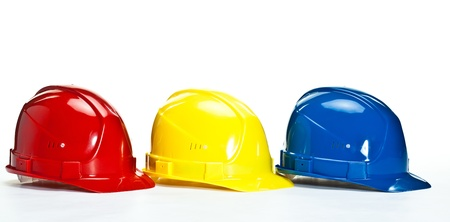 Industrial hardhats on white background; closeup of three multicolored construction hardhats photo