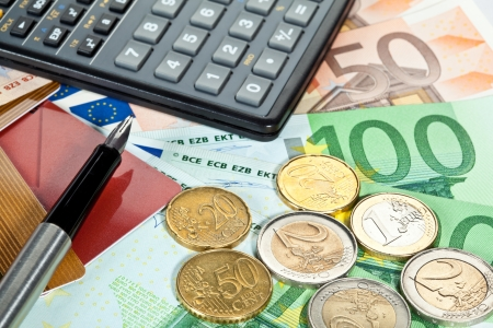 Concept of increase of capital: euro banknotes, coins, plastic cards, calculator and a pen Stock Photo