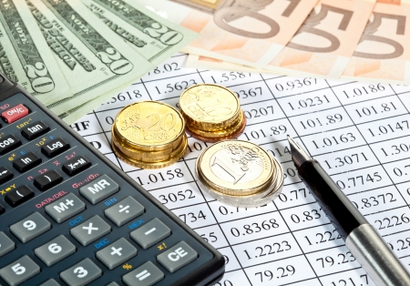 Financial analytics: banknotes, coins, calculator and a pen lying on a currency cross-rate table photo