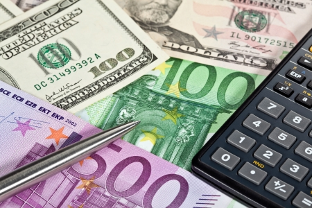 Euro and dollar banknotes, calculator and a pen photo