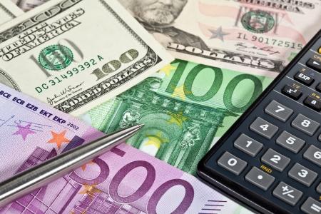 Euro and dollar banknotes, calculator and a pen photo