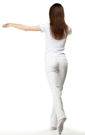 choreographic: Beautiful girl in white doing choreographic pas (battement tendus) - full length, white background, rear view