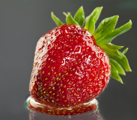 Juicy appetizing strawberry on grey background with reflection; studio shot Stock Photo - 14068010