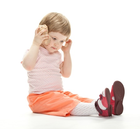 Adorable little girl playing with a seashell sitting on the floor, studio shot on white background photo