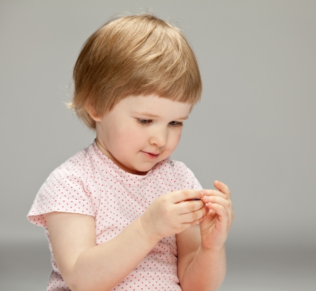 Curious little girl playing with a toy holding it in her hands, neutral background photo