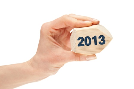 Happy New Year 2013 - hand showing number 2013 written on wooden polyhedron, isolated on white photo