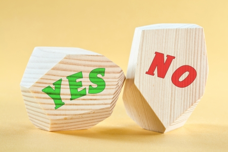 Yes  and  No  written on wooden blocks on yellow background photo