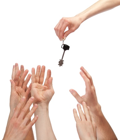 Many hands reaching out for key - concept of winning a house, apartment, etc.; isolated on white Stock Photo