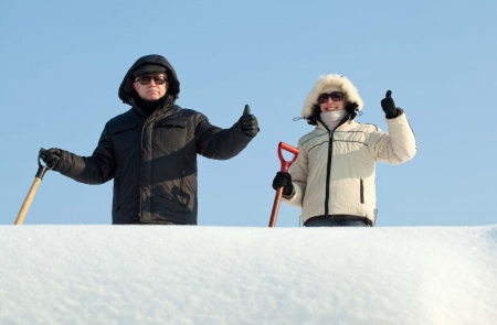 People with shovels for snow removal showing thumbs up photo