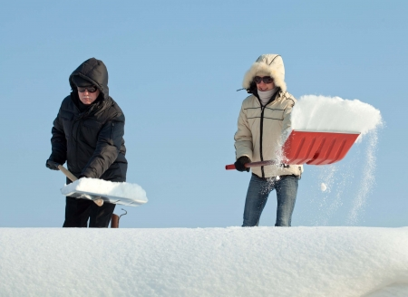 People shovelling snow on a roof against blue sky photo
