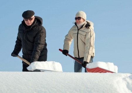 Happy people shovelling snow on a roof against blue sky