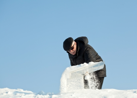 Man shovelling fresh snow from a roof after snowfall photo