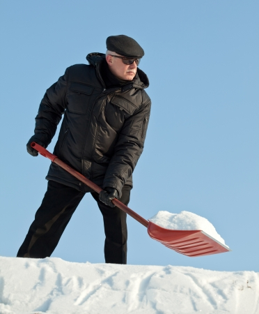 Man shovelling fresh snow from a roof after snowfall with a red shovel photo