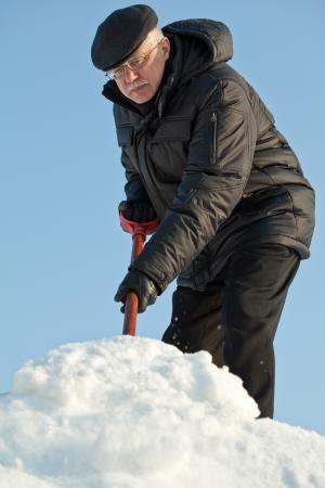 Man shovelling fresh snow from a road after hard snowfall