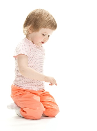 Cute little girl pointing at something, white background, copy space Foto de archivo