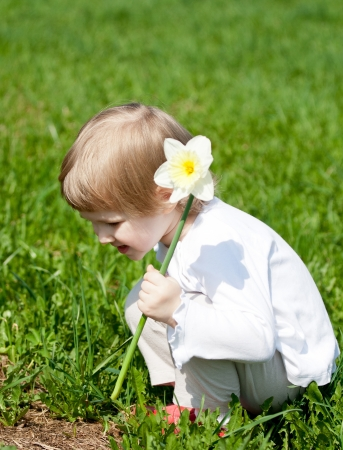 Happy little child with a flower playing in summer grass photo