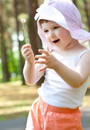Happy little girl playing with a flower in a park photo
