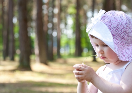 Little girl playing with a flower in a park photo