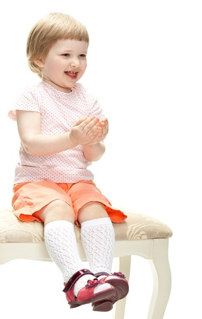 banquette: Merry playful little girl sitting on a banquette, studio shot isolated on white