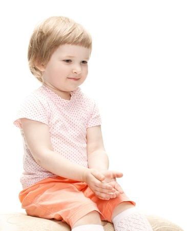 banquette: Cute little girl sitting on a banquette, studio shot isolated on white