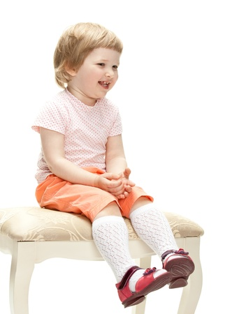 banquette: Happy laughing little girl sitting on a banquette, studio shot isolated on white