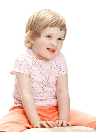 banquette: Happy smiling little girl sitting on a banquette, studio shot isolated on white