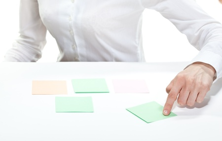 Womans hand pointing at paper note lying on a table photo
