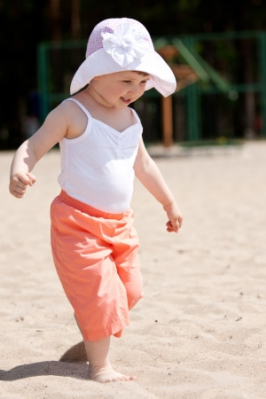 Happy little girl running along the beach enjoying sunny summer day photo