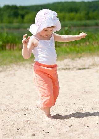 Adorable little girl playing on the bank of a lake photo