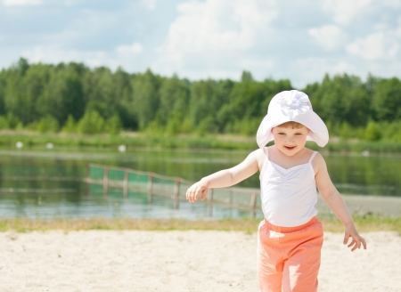 Happy little girl running along the bank of the lake enjoying sunny summer day photo