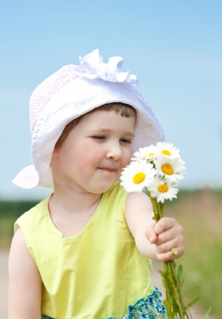 Happy beautiful little girl with bunch of summer flowers outdoors photo