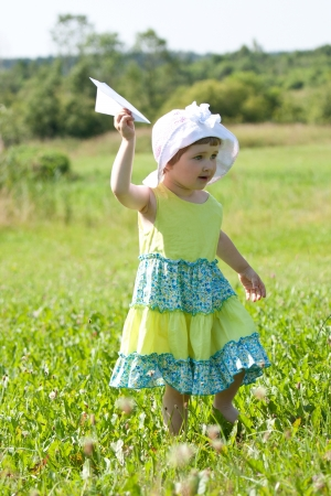 Happy little girl playing with a paper plane in summer field photo