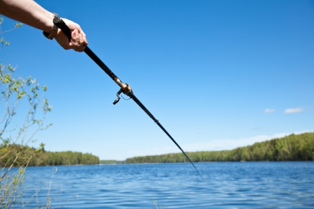 pastimes: Hand holding fishing rod over the water Stock Photo