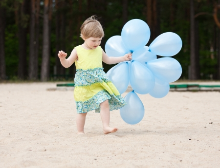 Adorable little girl running with balloons along the beach  photo