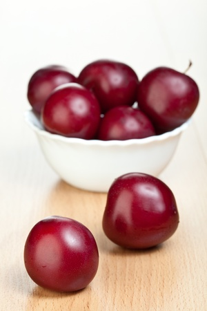 Ripe plums in a white bowl on a table photo