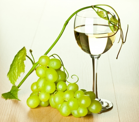 Branch of green grapes and glass of white wine photo