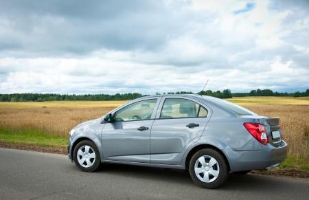 Auto op een weg tegen de bewolkte landelijke landschap Stockfoto