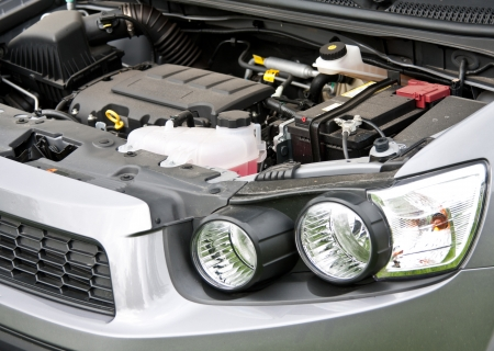 engine bonnet: An open bonnet and engine, storage battery of a modern car