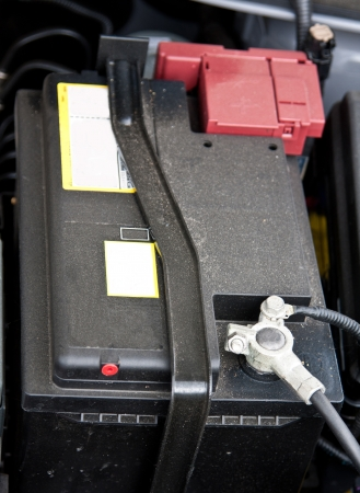 Accumulator (storage battery) under an open bonnet of a car